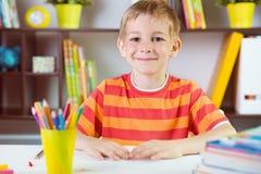 School boy at classroom desk making schoolwork. Elementary school boy at classroom desk making schoolwork stock photo