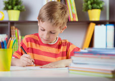 School boy at classroom desk making schoolwork. Elementary school boy at classroom desk making schoolwork royalty free stock images