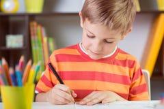 School boy at classroom desk making schoolwork. Elementary school boy at classroom desk making schoolwork stock photography