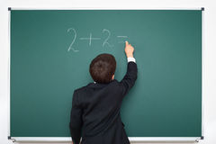 School boy decides examples math on chalkboard background, education exam concept Royalty Free Stock Photo