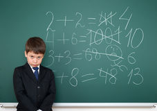 School boy decides examples math wrong on chalkboard background, education concept Royalty Free Stock Photos