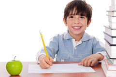 School boy doing his homework. With an apple beside him on white background Royalty Free Stock Photography