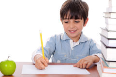 School boy doing his homework with an apple. Beside him on white background Royalty Free Stock Photo