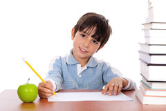School boy doing his homework with an apple. Beside him on white background Royalty Free Stock Images