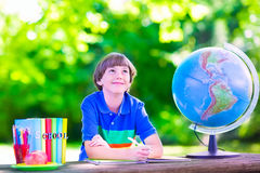 School boy doing homework in school yard. Child in school yard. Kids study. Happy laughing teenager student boy in the school garden reading books and having Royalty Free Stock Image