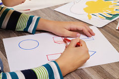 School Boy drawing geometric shapes on paper with Pencil. Kid, homework, education concept Stock Photography