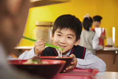 School boy eats noodles in school cafeteria Royalty Free Stock Image