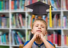 School boy in education library with graduation hat. Digital composite of School boy in education library with graduation hat royalty free stock photos