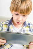 School boy with electronic tablet. Sitting in hall Stock Image