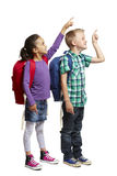 School boy and girl with backpacks pointing. 8 year old school boy and girl with backpacks pointing and smiling on white background Royalty Free Stock Photography
