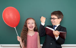 School boy and girl child with balloon on chalkboard background having fun Stock Image