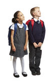School boy and girl looking up. 8 year old school boy and girl with backpacks looking up on white background Royalty Free Stock Image
