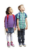 School boy and girl looking up. 8 year old school boy and girl looking up on white background Stock Photos