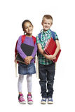 School boy and girl with packpacks holding books. 8 year old school boy and girl with backpacks holding books smiling on white background Royalty Free Stock Photos
