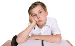 School boy lost in thought. A school student with head resting on one hand, siting in front of an empty book,  lost in thought, daydreaming, or thinking about Royalty Free Stock Photo