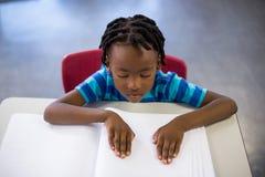 School boy memorizing the lesson in classroom Stock Photo