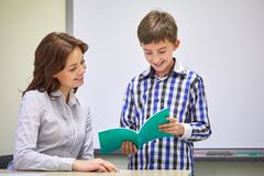 School boy with notebook and teacher in classroom Royalty Free Stock Photos