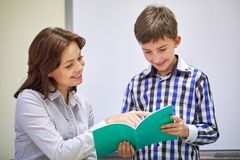 School boy with notebook and teacher in classroom Stock Photo