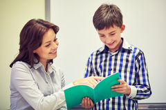 School boy with notebook and teacher in classroom Royalty Free Stock Images