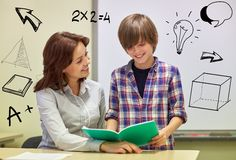 School boy with notebook and teacher in classroom. Education, elementary school, learning, examination and people concept - school boy holding notebook and Stock Photos