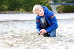 School boy playing with sand at schoolyard Stock Images