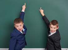 School boy point finger at blank chalkboard background, dressed in classic black suit, group pupil, education concept Royalty Free Stock Photos