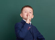 School boy point the finger near blank chalkboard background, dressed in classic black suit, group pupil, education concept Stock Image