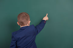 School boy point the finger near blank chalkboard background, dressed in classic black suit, group pupil, education concept Royalty Free Stock Photo