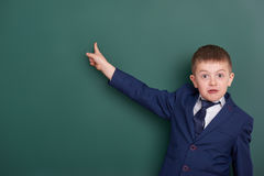School boy point the finger near blank chalkboard background, dressed in classic black suit, group pupil, education concept Stock Photo