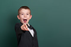 School boy point the finger near blank chalkboard background, dressed in classic black suit, group pupil, education concept Royalty Free Stock Image