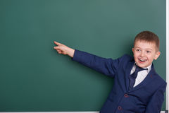 School boy point the finger near blank chalkboard background, dressed in classic black suit, group pupil, education concept Stock Photography