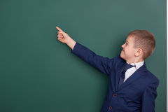 School boy point the finger near blank chalkboard background, dressed in classic black suit, group pupil, education concept Stock Images