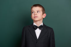 School boy portrait near green blank chalkboard background, dressed in classic black suit, one pupil, education concept Stock Image