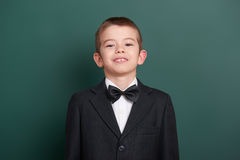 School boy portrait near green blank chalkboard background, dressed in classic black suit, one pupil, education concept Royalty Free Stock Photos