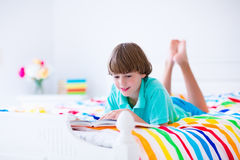 School boy reading a book in bed Stock Image