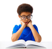 School boy reading book with surprise. Funny African American school boy reading book with surprise. Teenager with eyeglasses, shocked. Isolated, over white Stock Photography