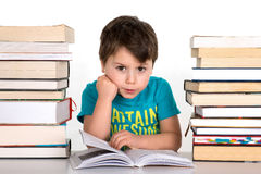 School boy reading surrounded by stack of books Stock Photos