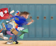 School Boy Running Late with Supplies in Hallway. A school boy is running late with school supplies falling out of his book bag in a hallway with lockers in the Royalty Free Stock Image