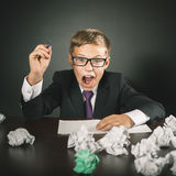 School boy shouts. Stress or depression. School classroom, many homeworks or exam driving his crazy. Child sits at the table with many crumpled papers. Kid Stock Photos