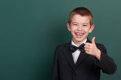 School boy show best gesture, portrait near green blank chalkboard background, dressed in classic black suit, one pupil, education Stock Images