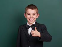 School boy show best gesture, portrait near green blank chalkboard background, dressed in classic black suit, one pupil, education Royalty Free Stock Photo