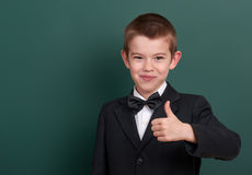 School boy show best gesture, portrait near green blank chalkboard background, dressed in classic black suit, one pupil, education Stock Image
