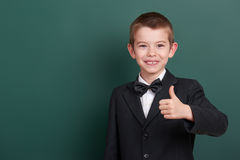 School boy show best gesture, portrait near green blank chalkboard background, dressed in classic black suit, one pupil, education Royalty Free Stock Photography