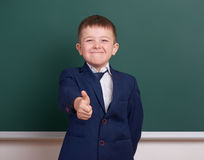 School boy show best gesture, portrait near green blank chalkboard background, dressed in classic black suit, one pupil, education Stock Photos