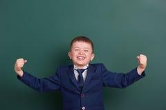 School boy show biceps muscles, portrait near green blank chalkboard background, dressed in classic black suit, one pupil, educati Stock Photo