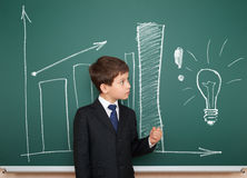 School boy show column graphs on board Royalty Free Stock Photo