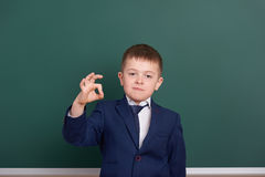 School boy show ok sign, portrait near green blank chalkboard background, dressed in classic black suit, one pupil, education conc Stock Images