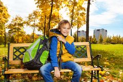 School boy sitting on bench in autumn park Stock Image