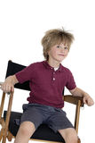 School boy sitting on director's chair over white background Stock Images