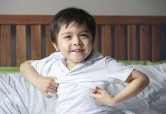 Free School Boy Sitting In Bed And Try To Wearing His Cloth With Smiling Face,Cute Kid Boy Getting Dressed And Get Ready For School, Royalty Free Stock Image - 188661156